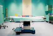 Operating room ready for operation with clock behind bed poster