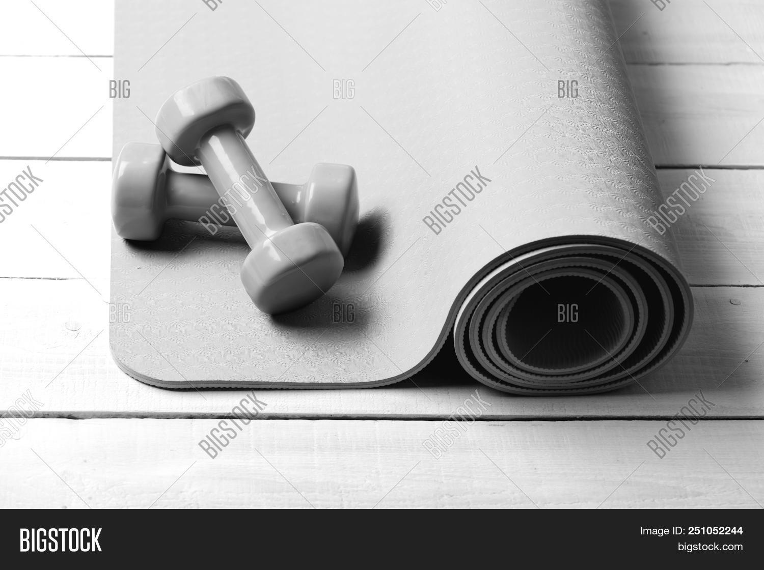 306d0bc8bad01 Sports and healthy lifestyle concept. Barbells in small size lie on rolled  purple yoga mat, close up. Dumbbells made of green plastic on light wooden  ...