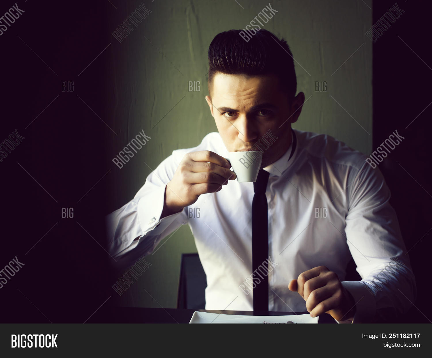a77dd93a626 Man young handsome elegant model wears white shirt black skinny necktie  sits at table drinks coffee and looks in camera indoor on grey background