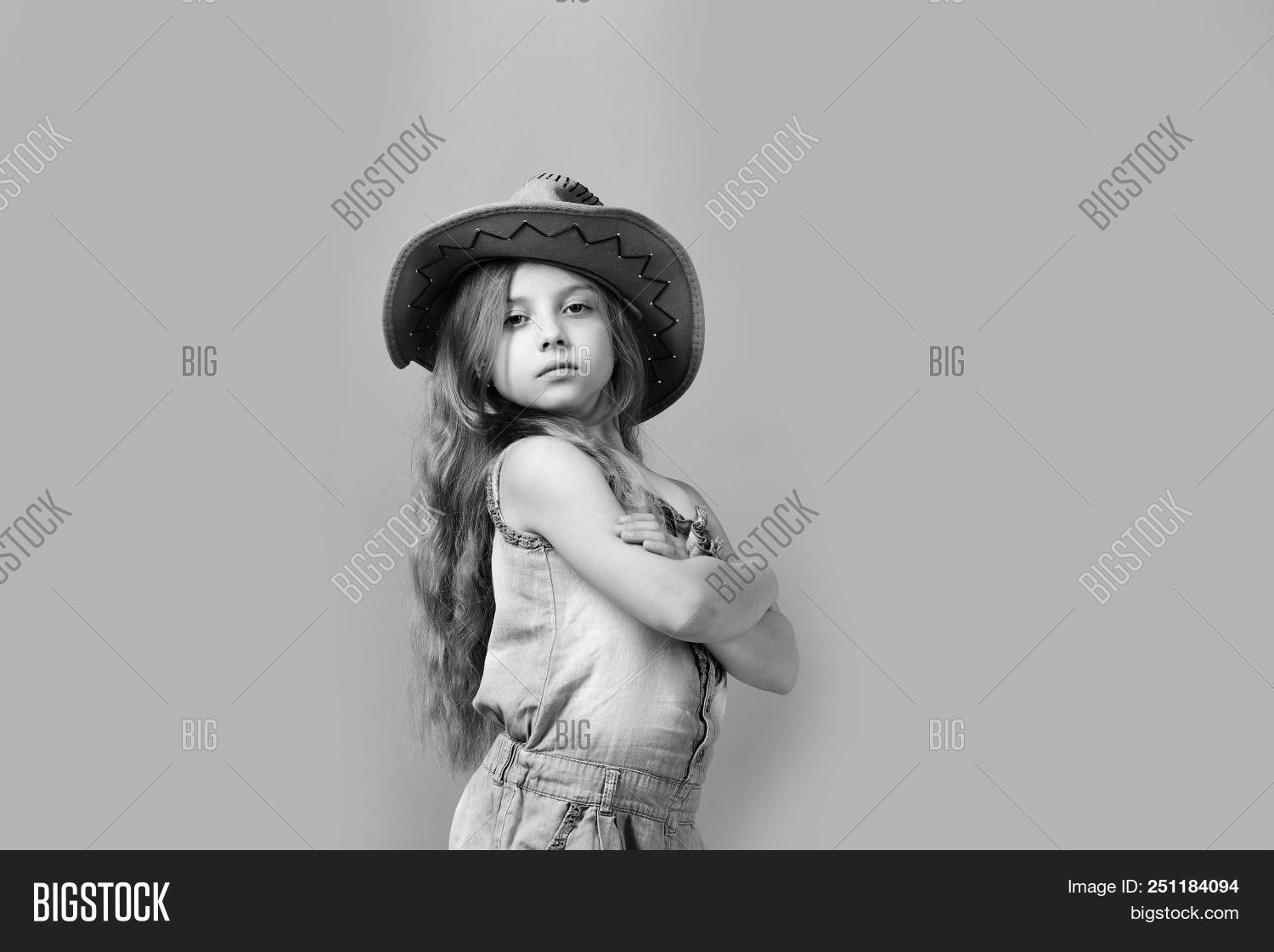 2c8e9342c78ee Fashion and casual style concept. Little lady in stylish clothes isolated  on green background. Girl in fancy outfit wears cowboy hat. Kid with  confident ...
