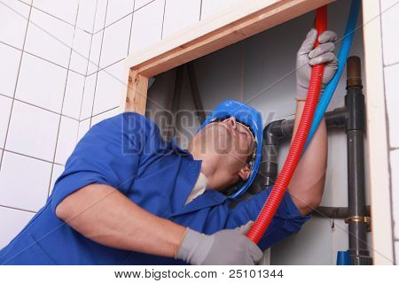 Plumber feeding flexible pipes behind a tiled wall