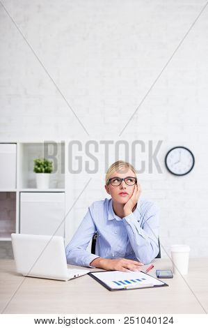 Tired Business Woman Sitting In Office And Dreaming About Something - Copy Space Over White Brick Wa