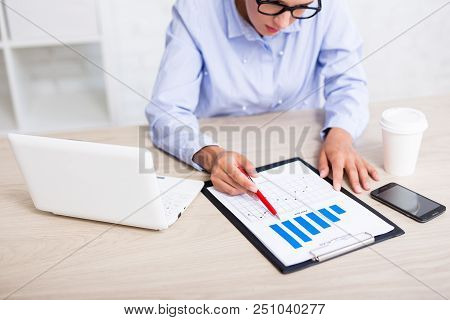 Business And Statistics Concept - Business Woman Sitting In Modern Office With Charts And Graphs
