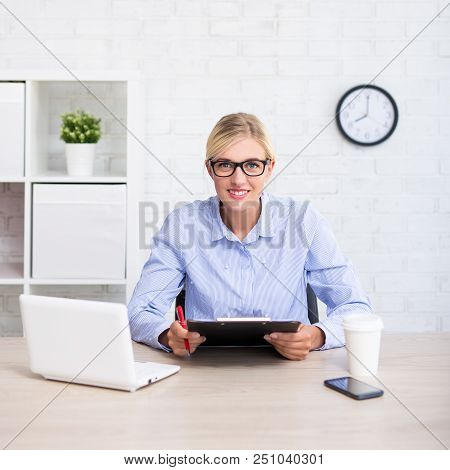 Portrait Of Business Woman Or Teacher Sitting In Office With Computer And Clipboard