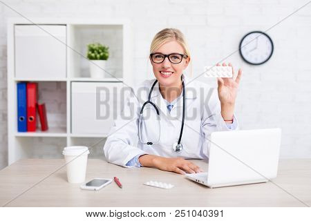 Female Doctor Pharmacist Showing Pills In Modern Office Or Store