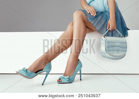 Beautiful Legs Woman Wearing Blue Dress With Blue Purse Hand Bag, High Heels Shoes Sitting On White