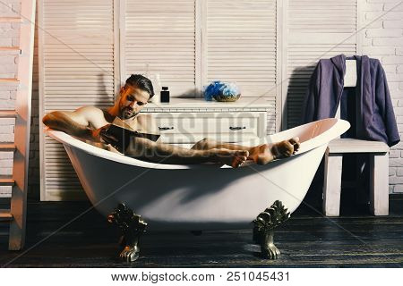 Macho sitting naked in bathtub and reading book. Man with beard and concentrated face. Guy in bathroom with toiletries, chair and stairs on background. Sexuality and relaxation concept. poster