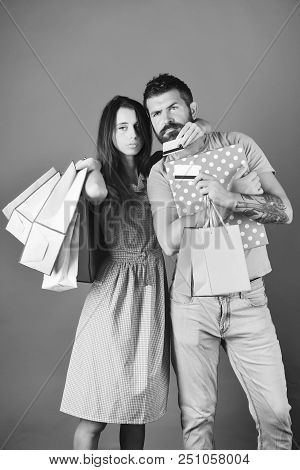 Man With Beard Holds Credit Card And Box. Couple In Love Holds Shopping Bags On Blue Background And
