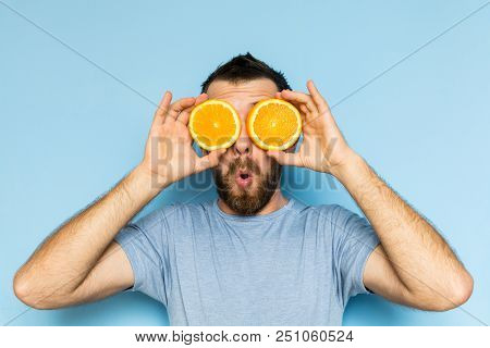 Young Man Holding Slices Of Orange In Front Of His Eyes