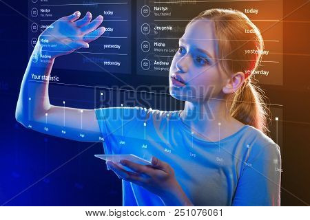 Transparent Screen. Calm Attentive Teenage Girl Holding A Thin Smartphone And Carefully Touching A T