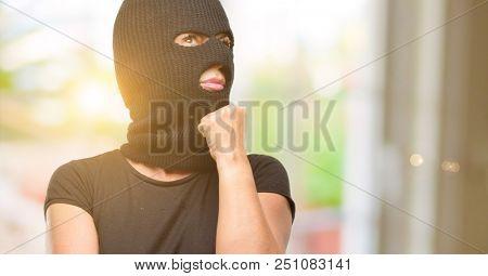 Burglar terrorist woman wearing balaclava ski mask thinking and looking up expressing doubt and wonder
