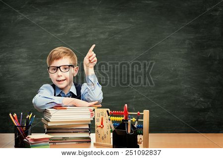 School Child In Classroom Over Blackboard Background, Boy Advertising Pointing Finger To Blank Chalk