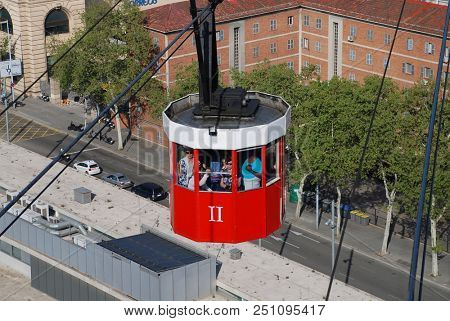 BARCELONA, SPAIN - APRIL 19, 2018: A vintage red cable car of the Transbordador Aeri del Port approaches Montjuic hill. The attraction was first opened in 1929.