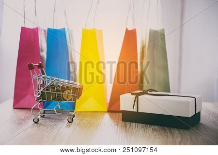 Model Of Shopping Cart On Wooden Floor And Gift Box And Shopping Bag, Online Payment And Shopping Co