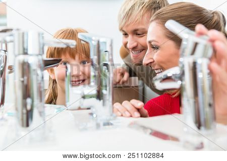Low-angle portrait of a happy family, looking for a new bathroom sink faucet in a modern sanitary ware shop with high-quality fixtures and appliances poster