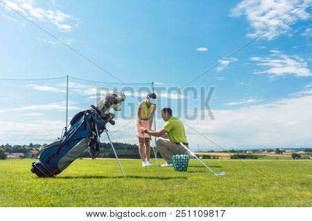Full length of an experienced male instructor teaching a young woman the correct grip of the golf club on a green field in summer poster