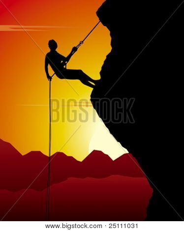 Mountain climber in action while sunset.