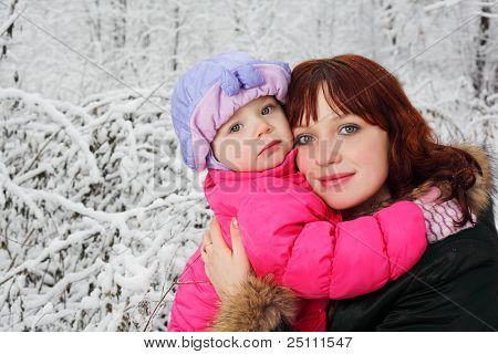 Young beautiful mother hugs little daughter in woods in snow at winter