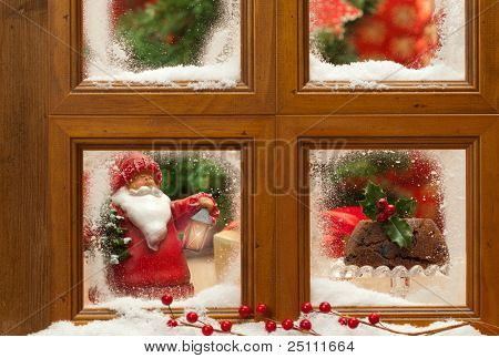 Festive Christmas frosty window with figgy pudding and father Xmas ornament, focus on Christmas pudding
