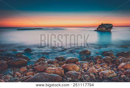 Beautiful sunset above sea, amazing landscape stony coastline with mystical mist over it in mild sunset light, nature of Lebanon