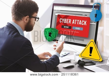 Man with smartphone and computer at table. Notification about threat of cyber attack on screens