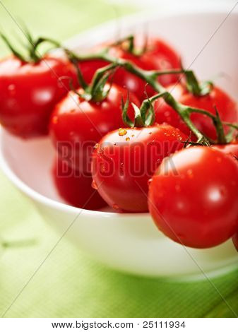 Fresh cherry tomatoes on the vine in a bowl