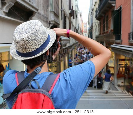 Young Boy With Digital Camera Takes Many Pictures Of A Narrow Street Called Calle In Italian Languag