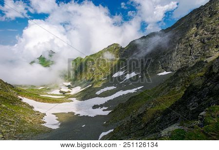 Spots Of Snow In The Valley With Rocky Cliffs. Distant Mountain Peak In The Cloud Formation. Gorgeou