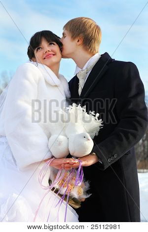 beautiful bride and groom hold pair of white doves at winter outdoors; man kisses woman