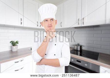 Young Man Chef Dreaming About Something In White Modern Kitchen