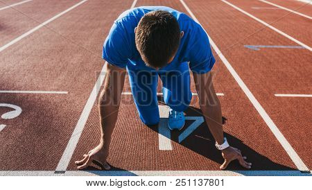 Horizontal shot of young male athlete at starting block on running track. Caucasian sprinter man in starting position for running to start a race at stadium. Sport, lifestyle and people concept. poster