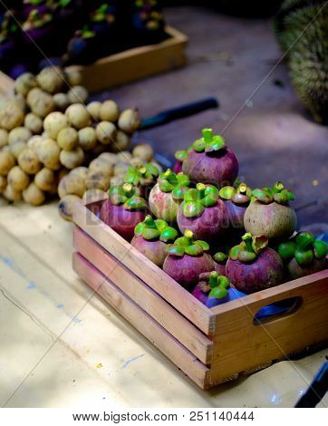 The Pile Of Mangosteen And Wollongong Are In A Small Wooden Crate. Put On A Light Yellow Surface Ins