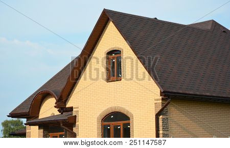 Roofing Construction House Building With Asphalt Shingles, Rain Gutter And Roof Ventilation. Close U