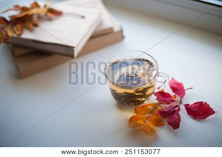 Autumn And Winter Concept. Tea In A Transparent Mug, A Stack Of Books, Yellow And Red Autumn Leaves,