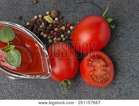 Glass Sauce-boat. Gravy Boat. Tomato Sauce On A Black Background