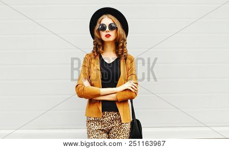 Elegant Young Woman Wearing A Retro Elegant Hat, Sunglasses, Brown Jacket And Black Handbag Clutch O