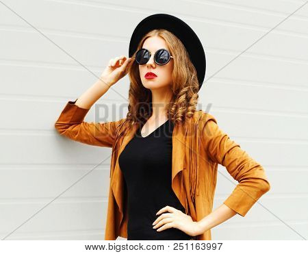Beautiful Woman Model Wearing A Black Hat, Sunglasses And Jacket Looking In Profile Over Urban Grey