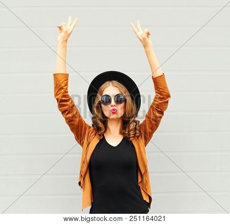 Cool Girl Wearing A Black Hat, Sunglasses And Jacket Raises Hands Up Over Urban Grey Background