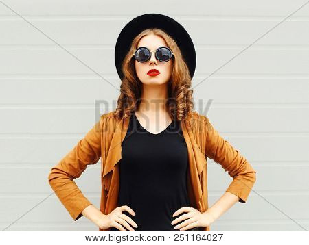 Elegant Woman Wearing Black Hat, Sunglasses And Jacket Over Urban Grey Background