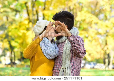 Dating And Autumn Love Concept. Couple In Love With Scarves Shows Heart Sign With Fingers. Girl And