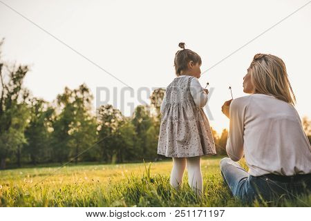 Outdoor Rear View Of Happy Girl Kid Playing With Her Mother Outside. Portrait Of Woman And Her Cute