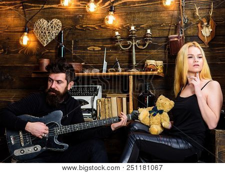 Couple In Love On Relaxed Faces Enjoy Romantic Atmosphere. Man Play Guitar While Lady Holds Teddy Be