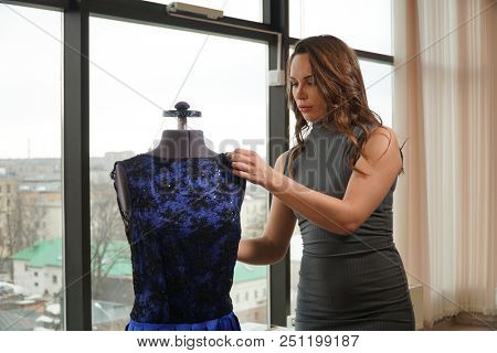 Young woman trying a dress on a mannequin, dressmaker in workroom.