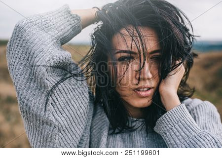Closeup Portrait Of Romantic Brunette Woman Posing Against Nature, Meadow Background With Windy Hair