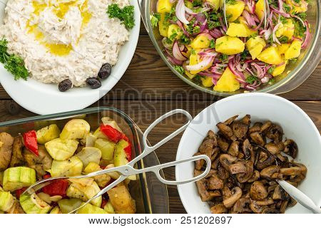 Overhead View Of Four Savory Vegetable Dishes Set On A Wooden Table With Stainless Steel Tongs And S
