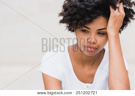 Beautiful Young Black Woman With Sad, Pensive, Reflective Look, Against White Wall Background With C