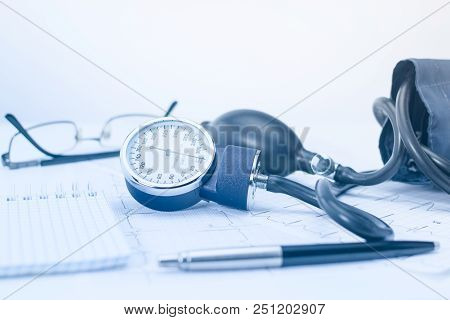Sphygmomanometer On The Working Table Of A Cardiologist. Tonometer, Electrocardiogram And Notepad Wi