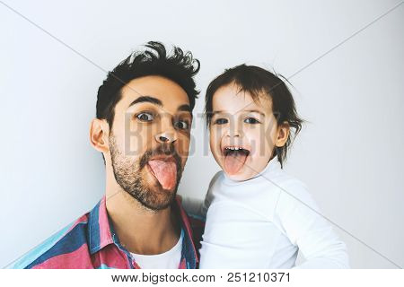 Happy father and beautiful little daughter sticking tongue out, isolated over a white background. Funny faces. Fatherhood. Dad play activities with his girl together shows tongues. Lifestyle family. poster