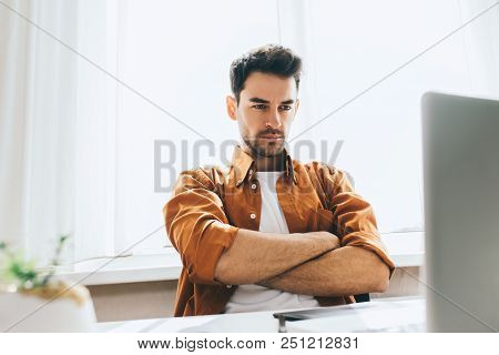Serious And Handsome Male Freelancer Sitting In Front Of The Computer With Serious And Thoughtful Ex