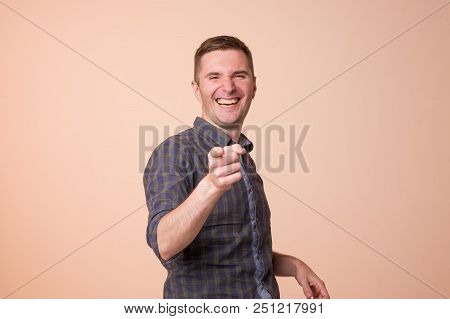 Portrait Of European Young Man, Laughing, Pointing With Finger At Someone. Positive Human Face Expre